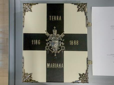 """Pie lasītavas otrajā stāvā goda vietā izlikta viena no astoņām grāmatas """"TERRA MARIANA"""" kopijām. Oriģinālu Rīgas turīgie pilsoņi bija izgatavojuši un uzdāvinājuši Romas pāvestam 19. gs. beigās (ja stāsts ir patiess)"""