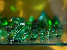 Stikla skapjos izlikta liela kolekcija ar dažādiem priekšmetiem no zaļa stikla